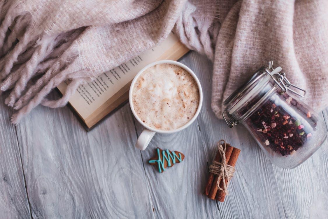 Café caliente con canela, libro y manta