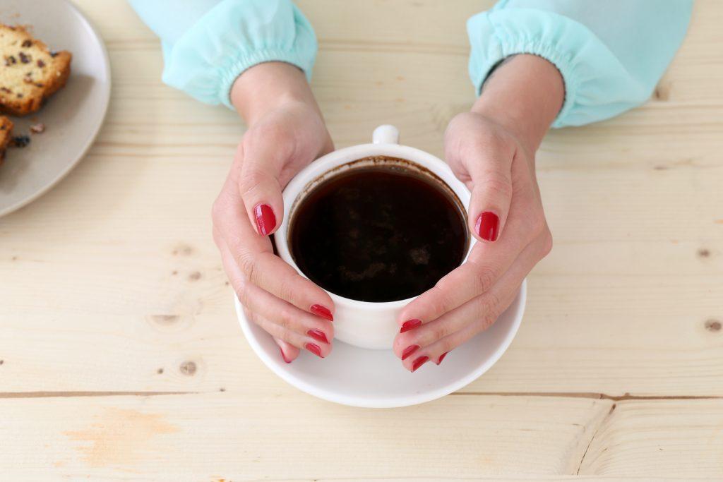 granos de café manos con taza de café cafemalist