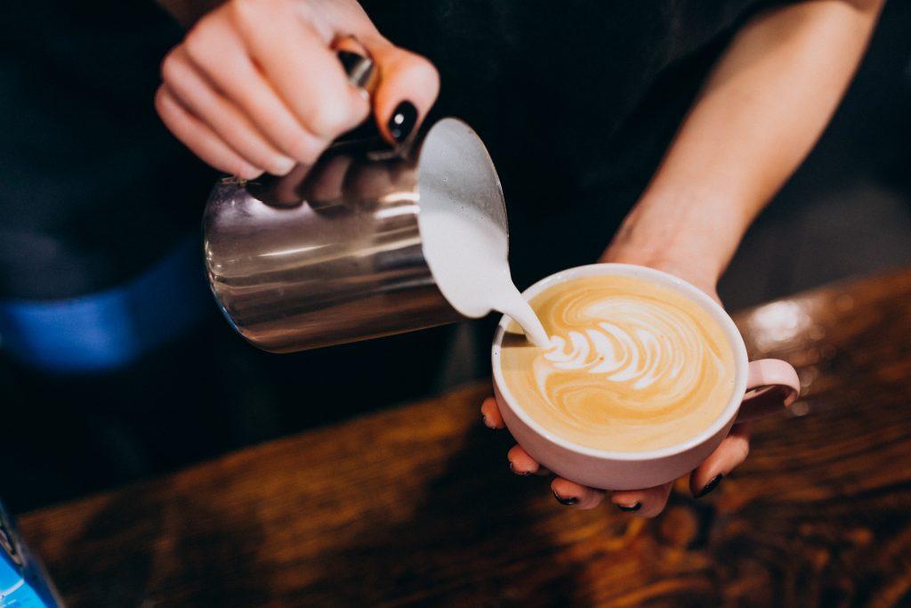 Barista sirviendo leche a un café