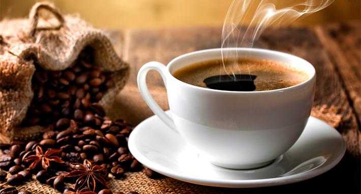 taza de café humeante con granos de café