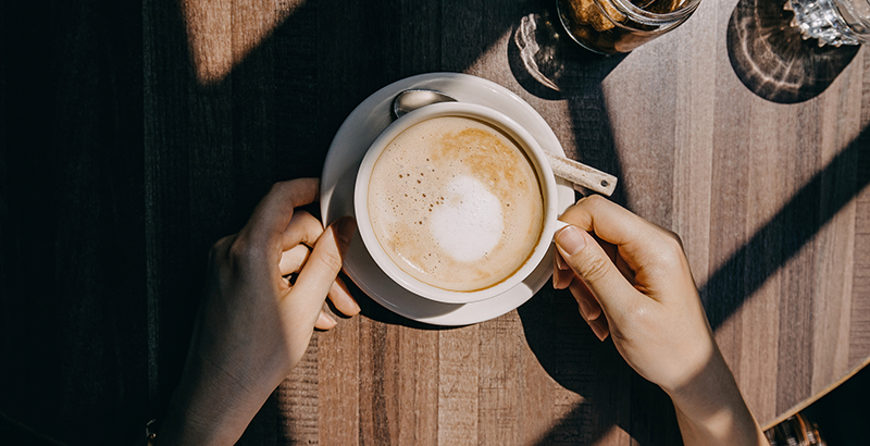 dos manos sosteniendo taza de café