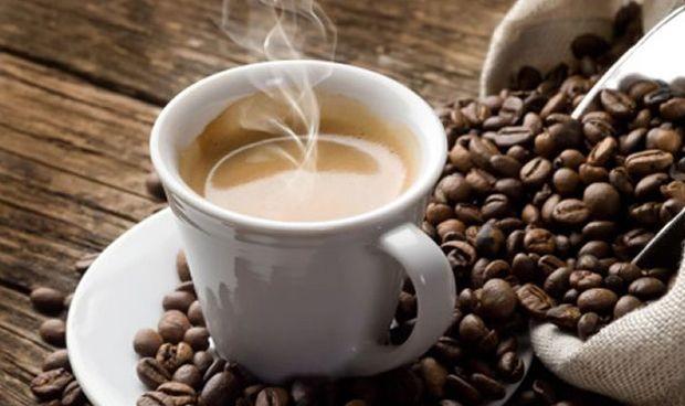 taza de café humeante con bolsa de granos de café