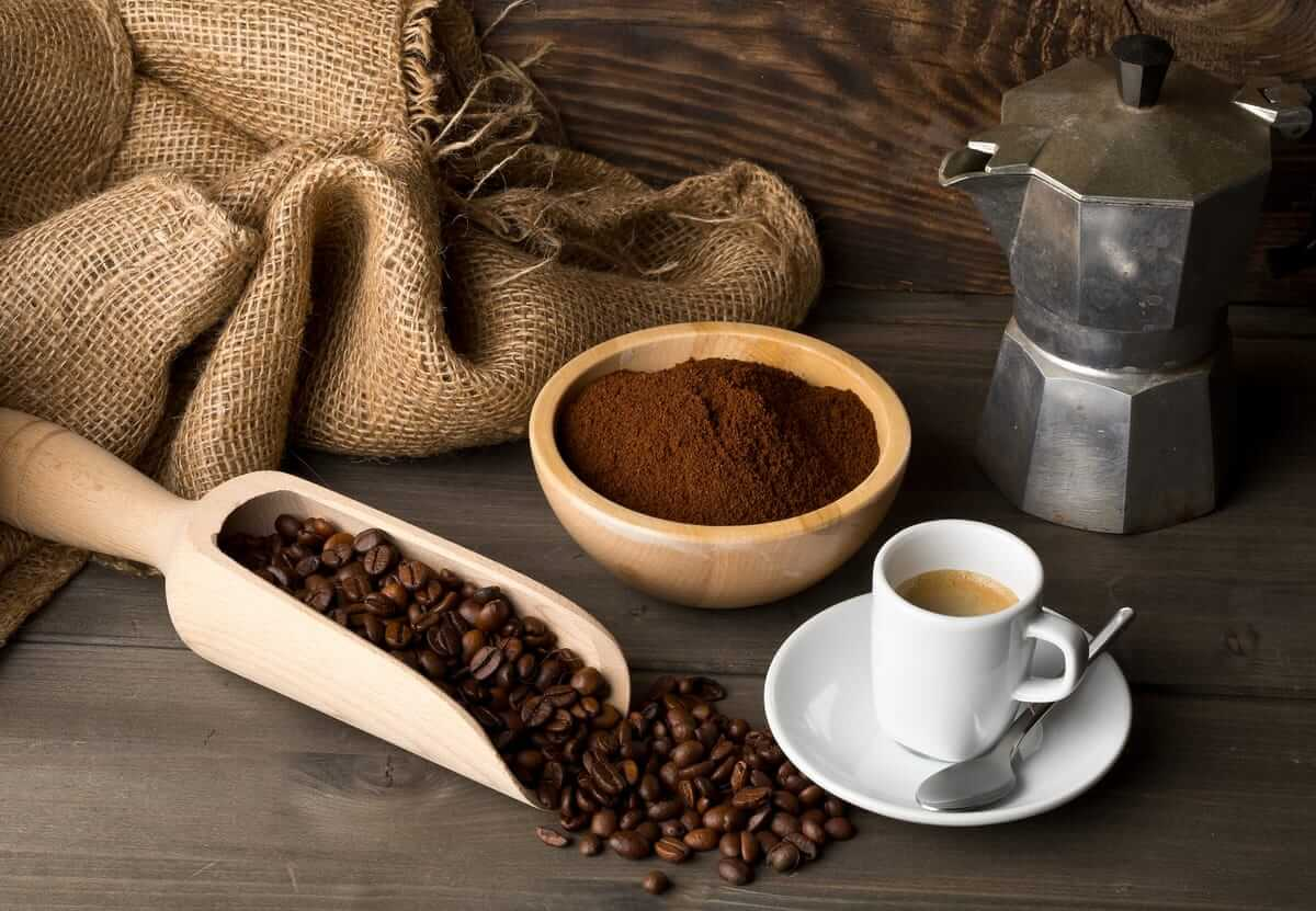 taza de cafe, cafetera, granos de cafe y cafe molid