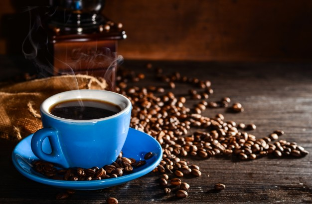 taza azul de café con granos de café
